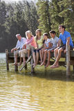 Three Generation Family Sitting On Wooden Jetty Looking Out Over Lake Royalty Free Stock Image