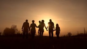 Three generation family walk in meadow at sunset stock footage