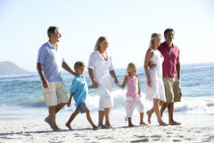 Three Generation Family Walking Along Sandy Beach Royalty Free Stock Photo