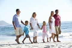 Three Generation Family Walking Along Sandy Beach Stock Images