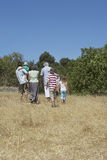 Three Generation Family Walking In Field Stock Images