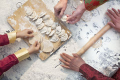 Three generation of women making dumplings, hands only Stock Photo