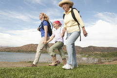 Three Generational Family Walking By Lake Stock Images