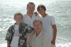 Three Generations. A family portrait of three generations in one family. Father, Son and grandsons. Standing on the shore of the ocean royalty free stock photos