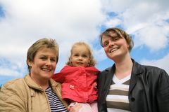 Three generations. Before a blue easily cloudy sky Stock Photography