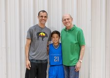 Three generations after baskeball game in Edmond, Oklahoma. Pictured is a vigorous seventy year-old man with his marathon running forty-one year-old son and his Stock Photography