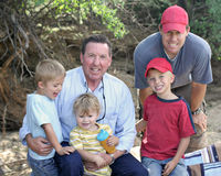 Three Generations of Boys. A grandfather sits with his son and 3 grandsons outdoors Royalty Free Stock Image