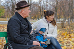 Three generations of a family at the park. With an elderly grandfather sitting on a wooden bench with his daughter and grandson stock image