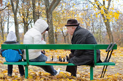 Three generations of a family playing chess in park beanch. Three generations  family playing chess with elderly men and his daughter sitting  park bench with Stock Photo