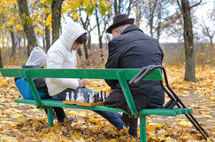 Three generations of a family playing chess in park beanch. Three generations family playing chess elderly men his daughter sitting park bench with chessboard Royalty Free Stock Images