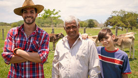 Three Generations Family Portrait Of Farmers In Farm. Everyday life for farmers with cows in the countryside. Peasants work in Latin America with livestock in Stock Images