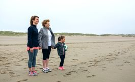Three generations female watching the sea. In autumn Royalty Free Stock Image