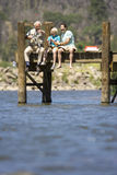Three generations fishing on jetty, boy (10-12) flanked by father and grandfather Royalty Free Stock Photography