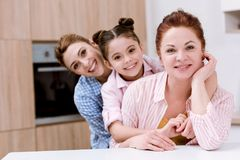 three generations of happy beautiful women standing in row together at kitchen and looking royalty free stock image
