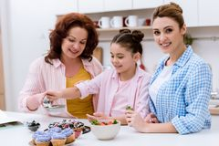 three generations of happy women pouring sugar onto tart with berries together royalty free stock photo