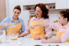 three generations of happy women preparing dough together royalty free stock images
