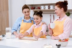 three generations of happy women rolling dough for cookies together royalty free stock photos