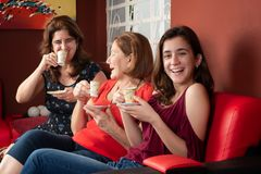 Three generations of hispanic women laughing and drinking coffee. At home attractive beautiful care celebration chat conversation daughter family female friend stock photo