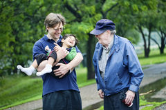 Three generations interacting together. At park Stock Images