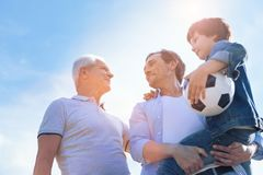 Three generations of men spending time outdoors. Men day. Low angle shot of a cheerful father holding his adorable son in arms while enjoying a pleasant Royalty Free Stock Photography