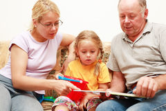 Three generations reading Royalty Free Stock Photos