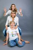Three generations with a striking resemblance. Three generations of attractive women with blond hair and a striking family resemblance posing together arm in arm Royalty Free Stock Images