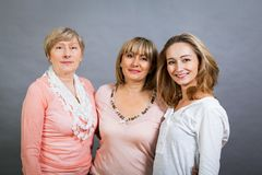 Three generations with a striking resemblance. Three generations of attractive women with blond hair and a striking family resemblance posing together arm in arm Royalty Free Stock Image