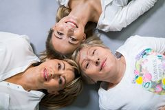 Three generations with a striking resemblance. Three generations of attractive women with blond hair and a striking family resemblance posing together arm in arm Royalty Free Stock Photo