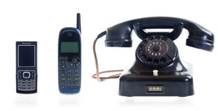 Three generations of telephones. From old dial phone to modern cell phone Stock Image