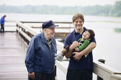 Three generations together. Three generations interacting together on the dock on misty morning Royalty Free Stock Photo