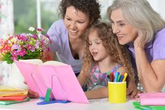 Three generations of women from one family doing homework. Together Royalty Free Stock Photography