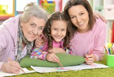 Three generations of women from one family lying on floor and dr. Awing picture together Stock Images