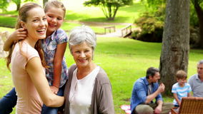 Three generations of women smiling at camera with men behind stock video footage