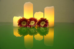 Three Gerbera flower and four lighted candles reflected in the green surface of the glass desk, Spa Style. Three Gerbera flower and four lighted candles Stock Image
