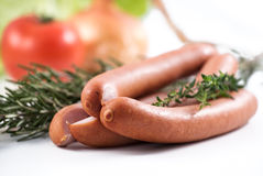 Three german sausage and herbs that were used to prepare them Stock Photo
