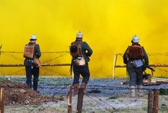 Three German soldiers-reenactors walk towards the yellow fume Royalty Free Stock Images