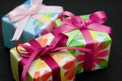 Three gift boxes. Three origami gift boxes on a black background. Focus on the pink ribbon of the box in front Stock Photos