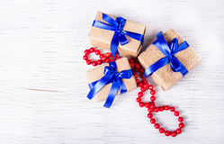 Three gift boxes with blue ribbons and coral beads. Surprise for beloved. Copy space. Royalty Free Stock Photography