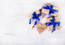 Three gift boxes with blue ribbons and valentines from a tree on a white background. Valentine`s Day. Copy space. Stock Photo