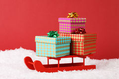 Three gift boxes with bow on red sled on snow on red background Stock Images