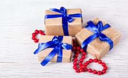 Three gift boxes made of kraft paper with blue ribbons and red coral beads. Gift boxes on a white background. Copy space Stock Images