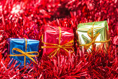 Three gift boxes on red tinsel Royalty Free Stock Photo