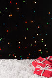 Three gift boxes on the snow with christmas lights on the background Royalty Free Stock Photos