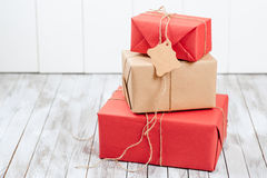 Three gift boxes with tag over wooden background. Royalty Free Stock Images