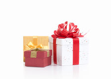 Three gift boxes tied with colored satin ribbons bow on white Royalty Free Stock Photos