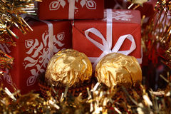 Three gift boxes and two golden golden sweets Stock Photos