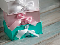 Three gift boxes, white, pink and turquoise. Wooden background. Royalty Free Stock Photography
