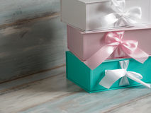 Three gift boxes, white, pink and turquoise. Wooden background. Stock Image