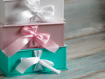 Three gift boxes, white, pink and turquoise. Wooden background. Stock Photos
