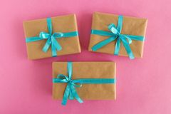 Three gift boxes wrapped of craft paper and blue ribbon on the pink background. Stock Image